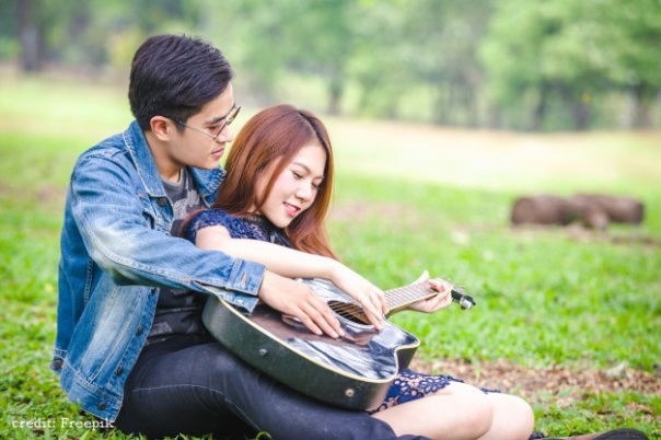 asian-couple-love-playing-acoustic-song-guitar-sitting-grass-park_39730-855
